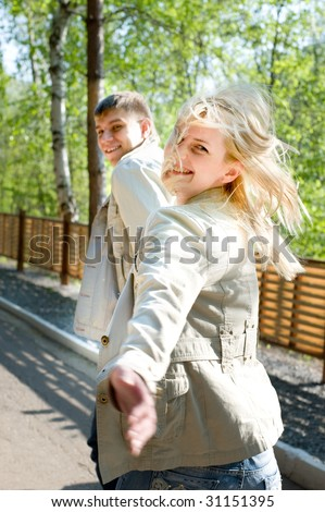 Young couple escaping and smiling. Run on park in good mood - stock photo