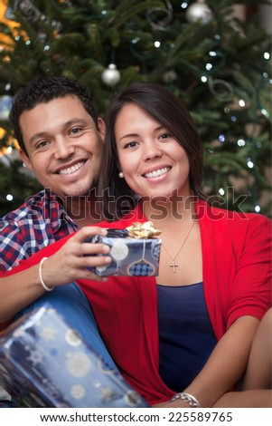 Young couple exchanging Christmas gifts and celebrating by the Christmas tree - stock photo