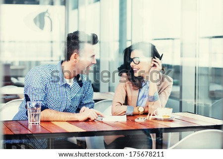 Young couple exchanging ideas and taking notes - stock photo