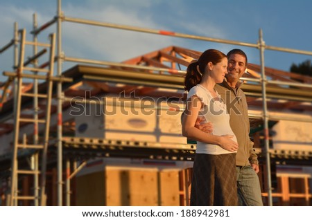 Young couple excited outside their new home. Concept buying a new house. - stock photo