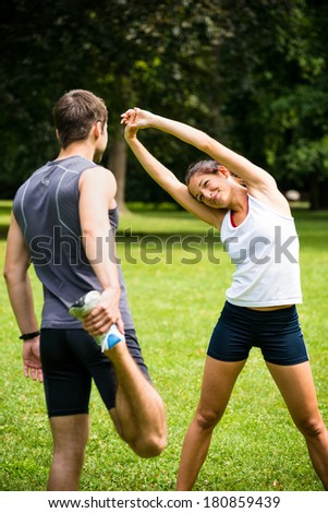 Young couple exercising and stretching muscles before sport activity - outdoor in nature - stock photo