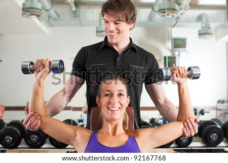 Young couple exercising in gym with weights, one of them is personal trainer - stock photo