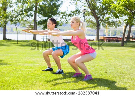 Young couple exercising outdoors - stock photo