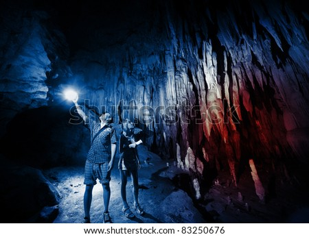 Young couple exploring huge cave with torches - stock photo