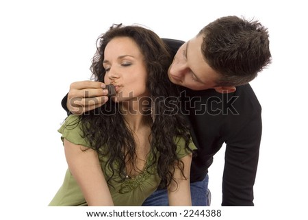 young couple feeding each other chocolate (white background) - stock photo