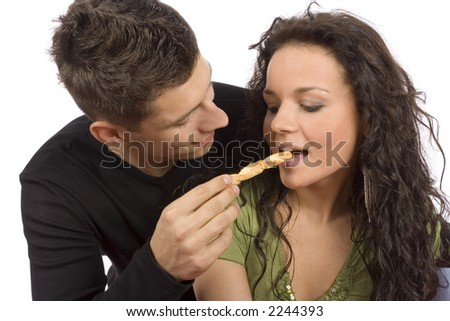 young couple feeding each other roll cake (white background) - stock photo