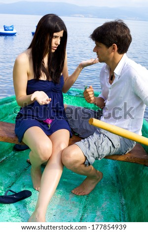 Young couple fighting on boat on lake in Italy - stock photo