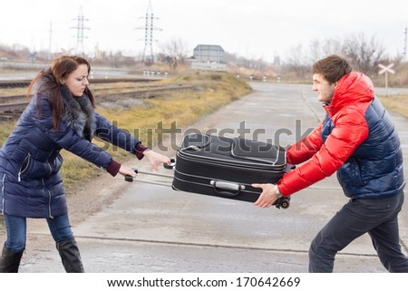 Young couple fighting over a suitcase pulling at it from either side on a road alongside a railway track - stock photo