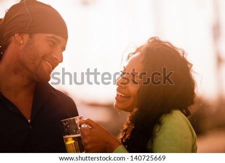 Young couple flirting while enjoying a Beer at Sunset at the beach in Venice California - stock photo