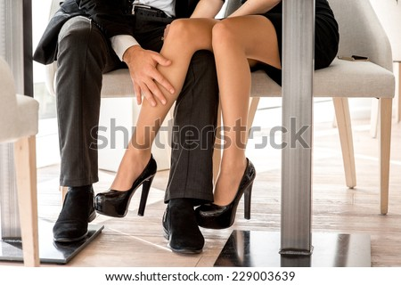 Young couple flirting with legs at the restaurant under the table - stock photo
