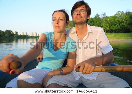 Young couple floating down the river on a boat with oars