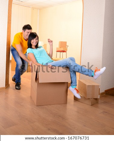 Young couple fooling around in new house on room background  - stock photo