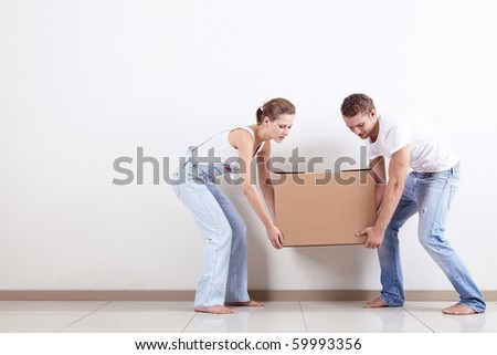Young couple gently drags a box - stock photo