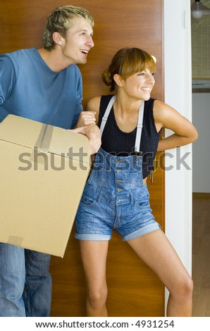 Young couple getting in to new flat. They're looking happy and surprised. Man is holding box
