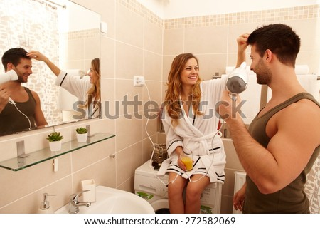 Young couple getting ready in the bathroom in the morning, drying hair, drinking orange juice. - stock photo