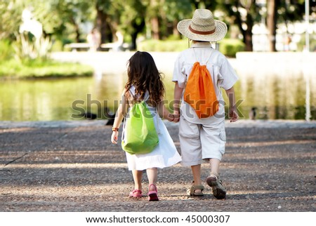 Young couple go on avenue in park - stock photo