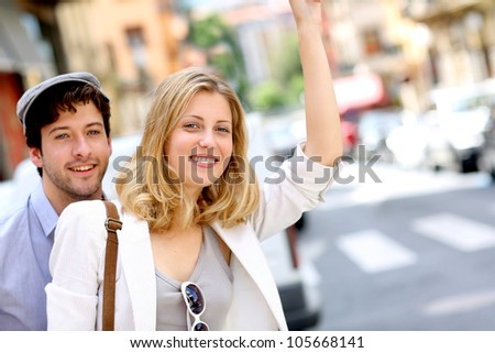 Young couple hailing for a taxi cab - stock photo