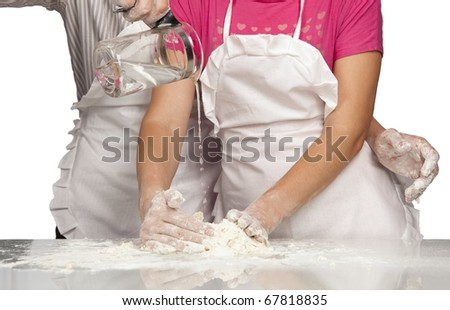 Young couple hands pouring water into flour (Focus on jug) - stock photo
