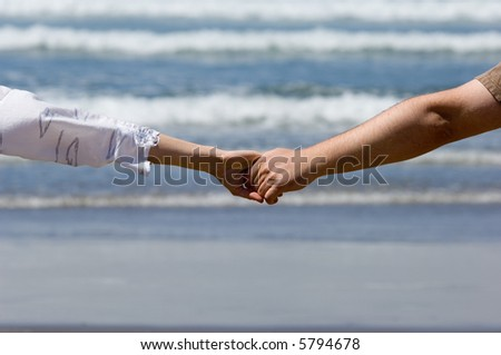 Young couple hands with the ocean waves background - stock photo
