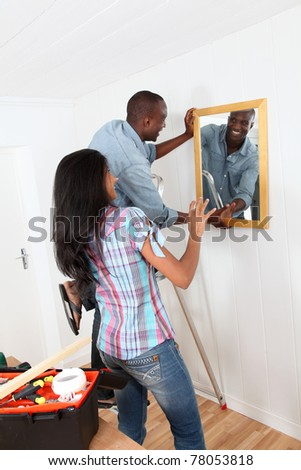 Young couple hanging mirror on the wall - stock photo
