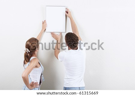 Young couple hanging up painting on the wall - stock photo