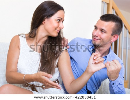 Young couple happily reconciling after quarrel at home. Focus on guy