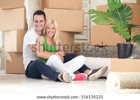 Young couple happy for their new home, hugging with boxes in background  - stock photo