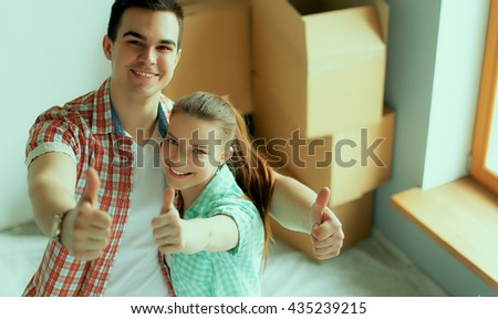 Young couple happy in their new modern design house showing thumbs up - stock photo