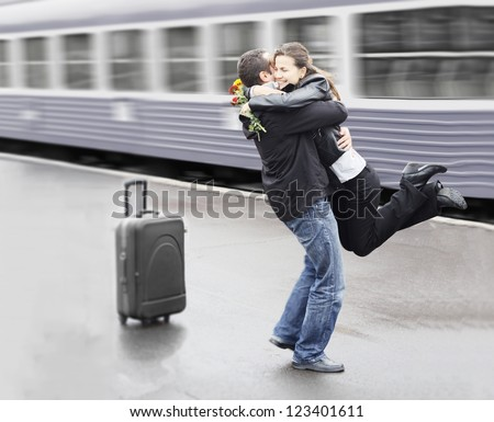 Young couple happy to meet again in the train station - stock photo