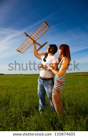 Young couple has holding the model airplane in their hands. They love each other and they are happy. - stock photo