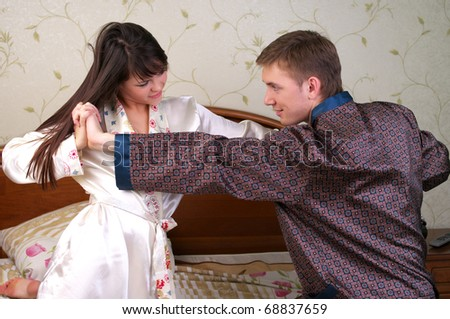 Young couple have a fun fight in bedroom - stock photo
