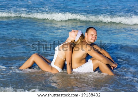 Young couple have a fun time on the tropical beach.