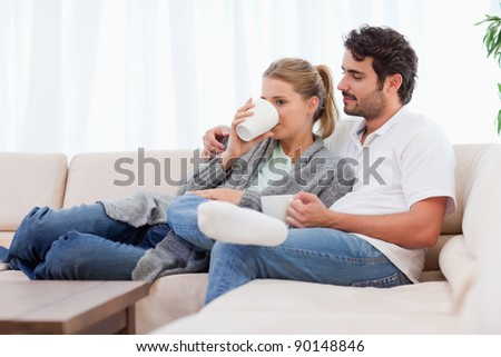 Young couple having a cup of tea in their living room - stock photo