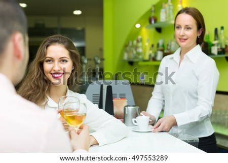 Young couple having a date with wine at bar. Focus on girl