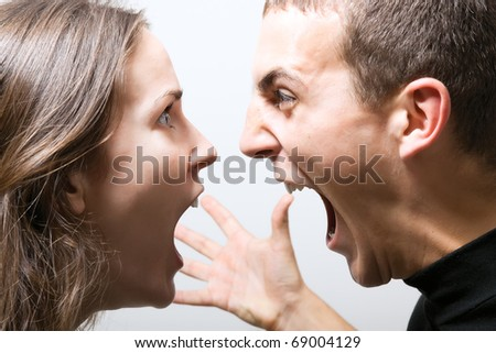Young couple having a fight, screaming at each other. - stock photo