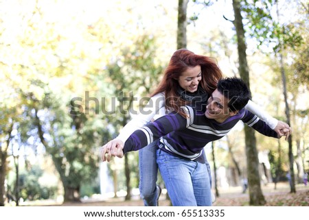 Young couple having a good time together at the park (selective focus with shallow DOF)
