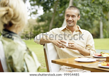 Young couple having a healthy breakfast in the garden. - stock photo