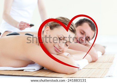 Young couple having a massage with hot stone against heart - stock photo