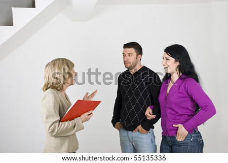 Young couple having a meeting with a senior estate agent and she showing them a new house - stock photo