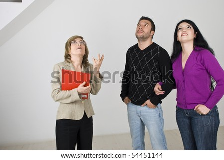 Young couple having a meeting with a senior estate agent and she showing them a new house,they all looking up at something - stock photo