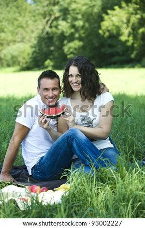 Young couple having a picnic - stock photo