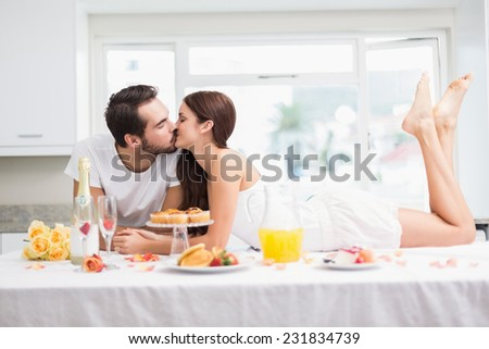 Young couple having a romantic breakfast at home in the kitchen - stock photo