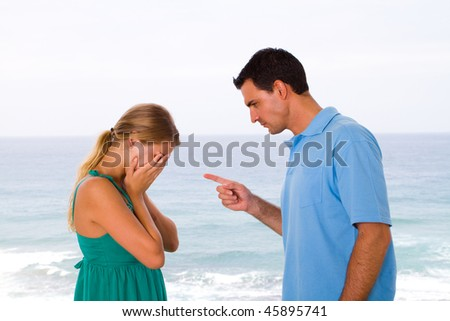 young couple having an argument background is sea view - stock photo