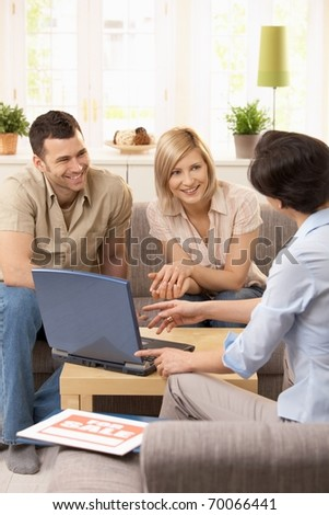 Young couple having appointment with estate agent in sunny living room.? - stock photo