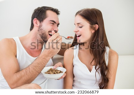 Young couple having breakfast in bed home in bedroom - stock photo