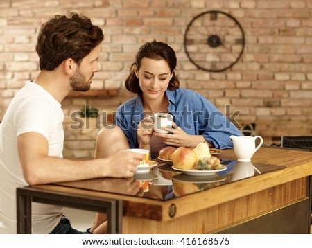 Young couple having breakfast in the morning at home. - stock photo