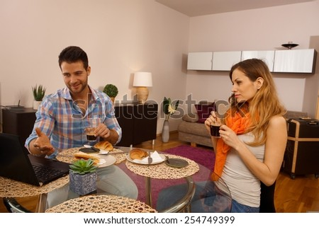 Young couple having breakfast on holiday in apartment. - stock photo