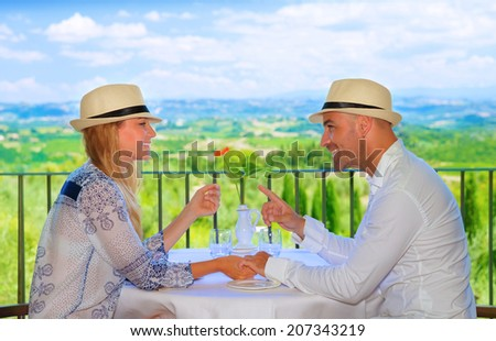 Young couple having breakfast on the terrace in restaurant, Europe, Italy, Tuscany, wonderful view, summer travel and tourism concept - stock photo