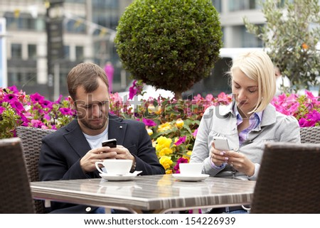 young couple having coffee in street cafe busy with their mobiles - stock photo