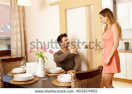 Young couple having dinner at home with friends, clinking glasses. - stock photo